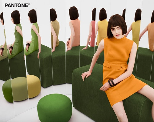 A model sitting on a green ottoman with an orange dress in a front of a range of mirror whose reflections show her in a different coloured dress