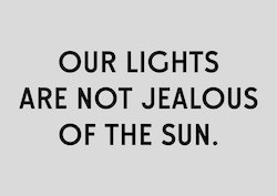 "A visual with the quote ""Our lights are not jealous of the sun"" on a grey background"