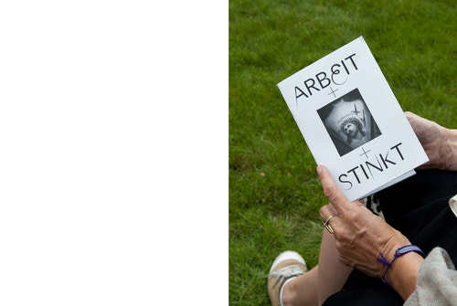 A woman holding a Ruhrtriennale brochure for Arbeit Stinkt