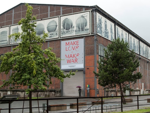 "Application of a poster designed for Ruhrtriennale quoting ""Make Love and Make War"" on a public building"