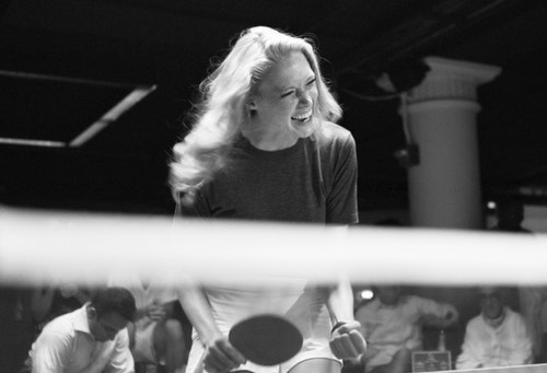 A blond girl playing ping-pong at Spin