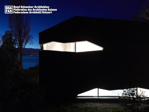 A poster with the building of the Swiss Architects Federation at night