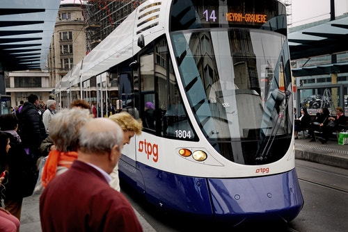A tram branded with the new logo arriving at a station
