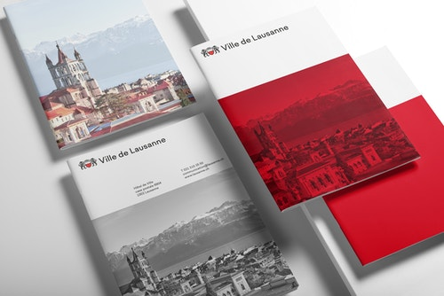 Set of City of Lausanne brandbook covers on a table