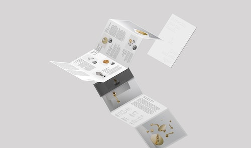 Two unfold brochures designed for Maison Vervloet flying in front of a light grey background