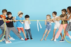 Children playing the tug-of-war on a blue background