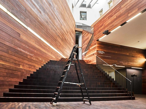 A picture of a ladder in front of the staircase of the MoMu building